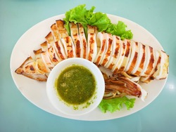 Squid grilled by charcoal fire, placed on a plate with spicy seafood dipping sauce, famous Thai seafood.