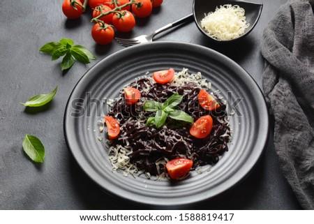 Squid Ink Pasta with cherry tomatoes , parmesan, basil leaves. Black spaghetti, black organic noodles . Mediterranean gourmet food.