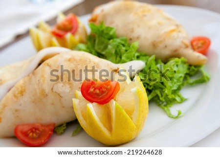 Squid stuffed with seafood on white plate in restaurant