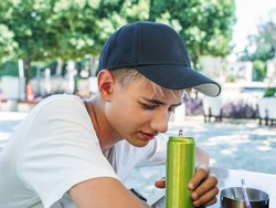 Squinting, a 15-18 year old teenager holds a metal aluminum can for drinks. Soda, energy drink, seltzer or iced coffee