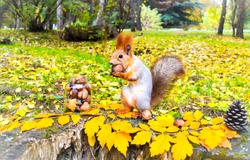 Squirrel in autumn park forest. Squirrel with nuts in autumn forest park scene