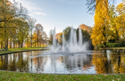 Squirting fountains in the pond of the Valkenberg park in the Dutch city of Breda in the fall season.