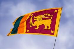 Sri Lanka flag isolated on sky background. National symbol of Sri Lanka. Close up waving flag with clipping path.