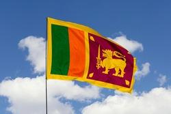 Sri Lanka flag isolated on the blue sky with clipping path. close up waving flag of Sri Lanka. flag symbols of Sri Lanka.
