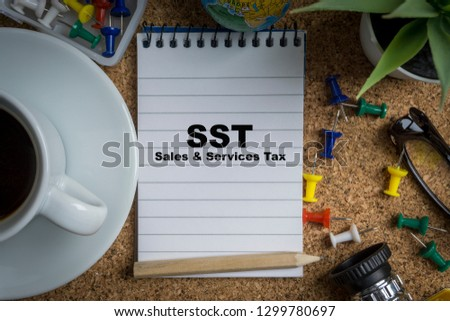 SST inscription written on book with globe,eyeglasses, calculator, camera, pencil and vase on wooden background with selective focus and crop fragment. Business and education concept Stock fotó ©