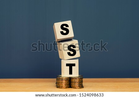 SST. Sales and Service Tax on wooden block on stacked coins #1524098633