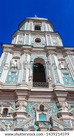 St Andrew's Church, Kiev, Ukraine. The church is small and painted blue and white, with many decorations on it's facade. Picture taken from underneath the church, with a view on the front side.