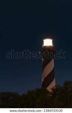 St. Augustine Lighthouse Florida at night with the star in the background.  Long Exposure with the fresnel lens lit and sending a warning to sailors out to sea. #1386933530