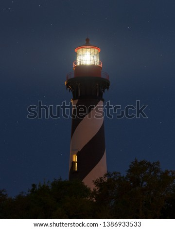St. Augustine Lighthouse Florida at night with the star in the background.  Long Exposure with the fresnel lens lit and sending a warning to sailors out to sea. #1386933533