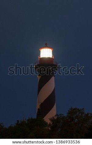 St. Augustine Lighthouse Florida at night with the star in the background.  Long Exposure with the fresnel lens lit and sending a warning to sailors out to sea. #1386933536