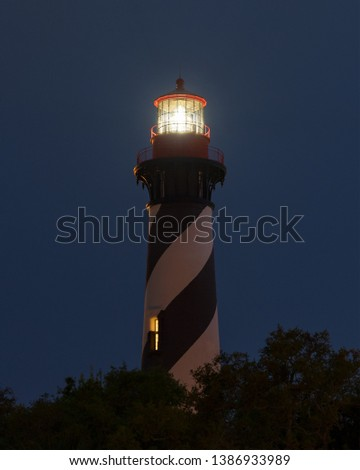 St. Augustine Lighthouse Florida at night with the star in the background.  Long Exposure with the fresnel lens lit and sending a warning to sailors out to sea. #1386933989
