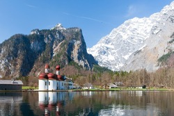 St Bartholomew church with a red onion-shaped dome located on the bank of Lake Konigsee is the highlight, reflection of the church on the clear water surface is a breathtaking sight of nature.