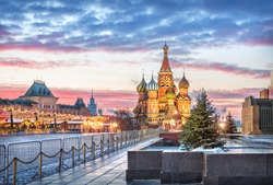 St. Basil's Cathedral, GUM store on Red Square in Moscow under a pink dawn sky and Christmas trees