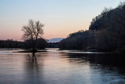 St. Croix River at sunset with the reflections of a lone tree and river bluffs. Pink sky of twilight.