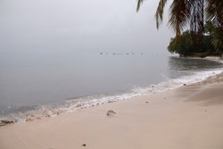 St. James, Barbados - April 10 2021: Thick ash from St. Vincent and the Grenadine's Soufriere volcano eruption turns the sky and ocean grey on an east coast beach with a thick unbreathable haze.