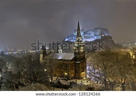 St. John's church, Edinburgh Castle, and surrounding city skyline illuminated at night during winter snow fall.
