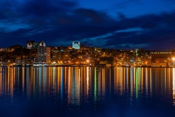 St. John's, waterfront harbour at night during the blue hour. The lights on the water are bright yellow and orange which are reflecting from the skyline in the stillness of the smooth water.