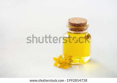 St. John's wort extract oil in a bottle on a gray background. Vegan food. Natural cosmetics