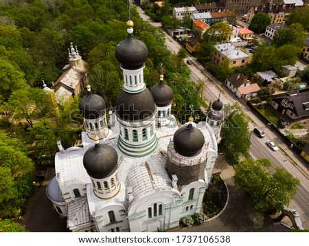 St. John the Forerunner orthodox church among cemetery with green trees with dome under reconstruction aerial stock photo