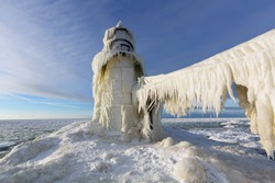 St. Joseph Pier Lighthouse frozen in winter. The catwalk is draped with ice curtains and the light is encased from furious Lake Michigan storms and winds