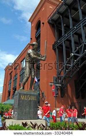"""ST LOUIS – MAY 23: Baseball fans stand near the statue of Stan """"The Man"""" Musial outside of Busch Stadium on May 23, 2009 in St Louis, Missouri. Busch Stadium is the home of the Saint Louis Cardinals."""