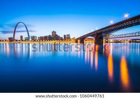 st. louis skyscraper at night with reflection in river,st. louis,missouri,usa.