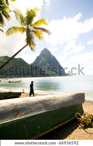 St. Lucia island view of famous twin piton mountain peaks from Soufriere beach native fishing boats Rasta man fisherman silhouette  in Caribbean Sea