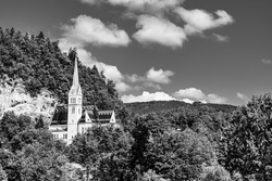 St. Martin Parish Church in Bled, Slovenia. Church of St Martin, a small white neo-gothic church surrounded by green trees on top of a rock hill