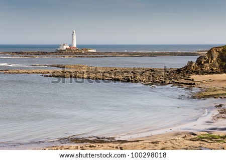 St Marys lighthouse across sandy bay / St Marys Lighthouse across sandy bay and rocks from cliff tops