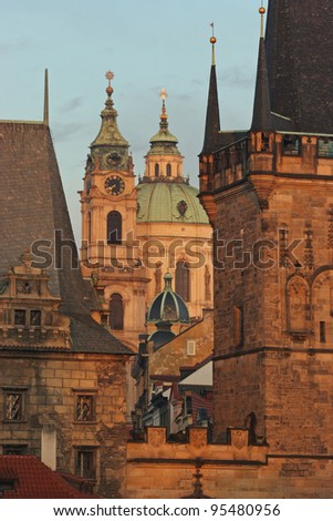 St. Nicholas church and towers of Charles bridge in Prague, close to Prague Castle and Vltava river