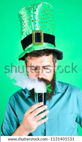 St. Patrick concept. Saint Patrick celebration. Funny man in leprechaun hat with beard drinks beer in bar. Man with beard in St. Patrick's suit. Handsome bearded man celebrate St. Patrick's Day.Clover