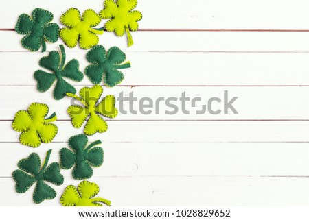 St.Patrick's day background with felt four-leaf clover on white wooden table. Space for text, top view. Lucky irish shamrock.