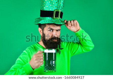 St. Patrick's Day. Bearded man in leprechaun hat. Portrait of pensive man with green beer. Bearded leprechaun. Happy Irish leprechaun with black beard. Bearded man. Green background. Irish tradition.