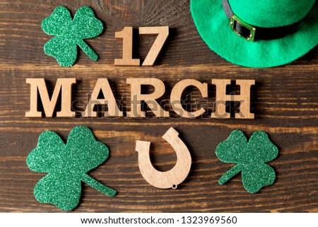St.Patrick 's Day. celebration. green leaves of clover and horseshoe and the text of March 17 on a brown background. top view.