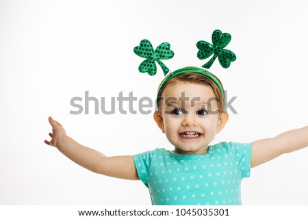 St.Patrick's day clover head decoration on a close up of an excited toddler girl