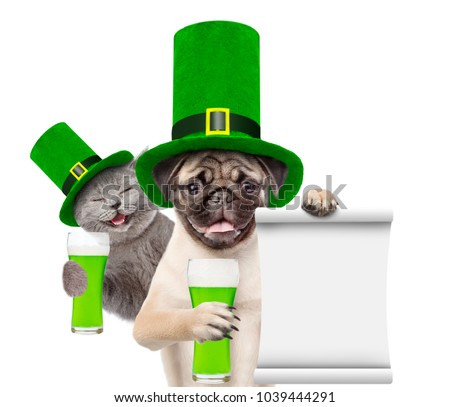 St Patrick's Day concept. Happy cat and puppy with a glass of green beer and  with empty list. isolated on white background