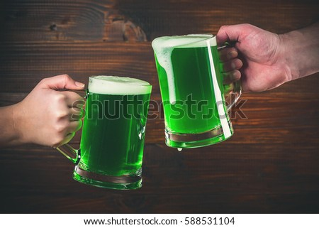 St Patrick's Day concept two mug on hands green beer against wooden background