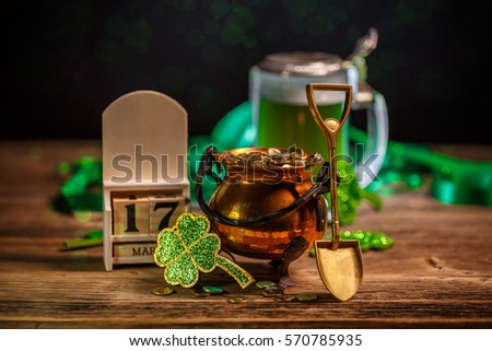 St Patrick's Day concept with pot of gold, shamrock and block calendar on wooden background.