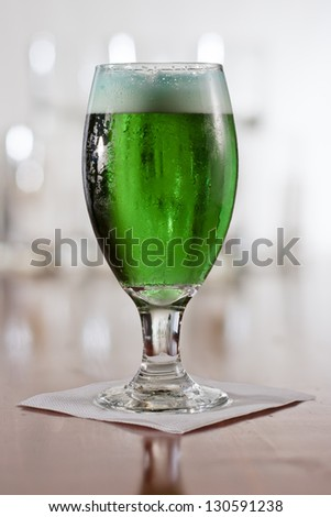 St. Patrick's day green beer served in a chalice on a busy bar