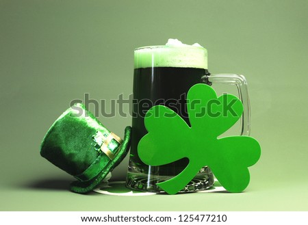 St Patrick's Day green beer with shamrock and Leprechaun hat against green background.