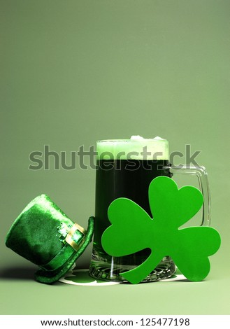 St Patrick's Day green beer with shamrock and Leprechaun hat against green background. Vertical portrait orientation.