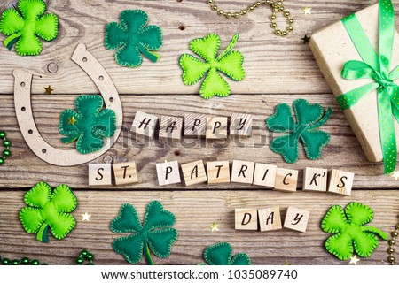 St.Patrick's day greeting message with clover leaves, horseshoe and gift box on old wooden boards. St.Patrick's day holiday symbol.