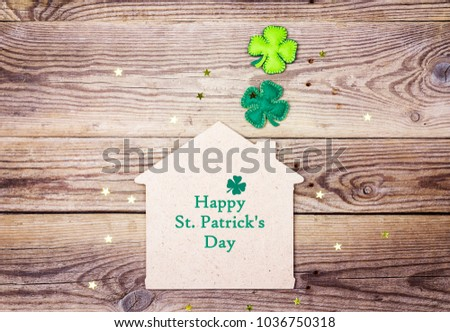 St.Patrick's day greeting message with lucky home symbol and four-leaf clover on wooden background. St.Patrick's day holiday symbol.