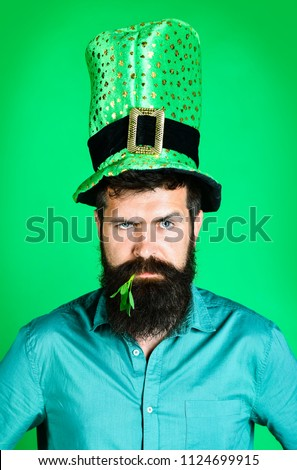 St Patrick's Day. Serious bearded man with clover in mouth. Bearded man in green men hat celebrate Patricks Day. St Patrick's Day Party. Saint Patrick. Ireland tradition. Saint Patrick's Day symbols.