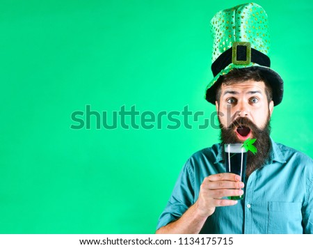 St Patrick's Day. Surprised man holds glass of beer on St.Patrick's day. Saint Patrick's Day concept - bearded man in leprechaun hat pours beer. St Patrick's Day green beer with shamrock. Copy space.