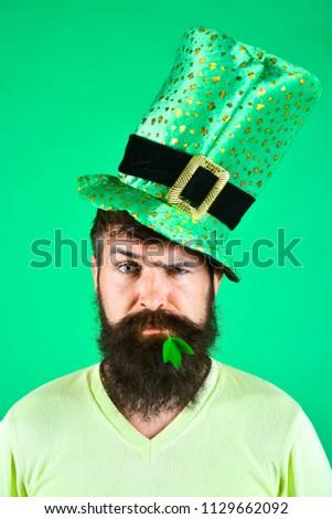 St. Patrick's man. St. Patrick concept. Saint Patrick celebration. Handsome bearded man celebrate St. Patrick's Day. Guy in leprechaun hat with clover in mouth. Ireland tradition. Patrik's day symbol.