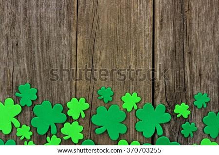 St Patricks Day bottom border of shamrocks over a rustic wooden background