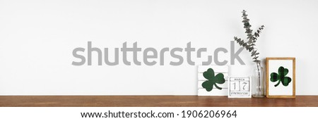 St Patricks Day decor on a wood shelf. Shabby chic wood signs, calendar and green branches against a white wall banner. Copy space.