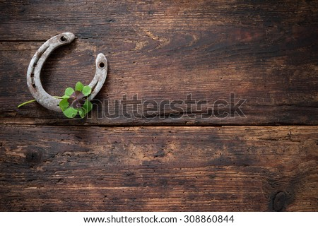 St.Patricks day. Four leaved clover and a horseshoe on wooden board