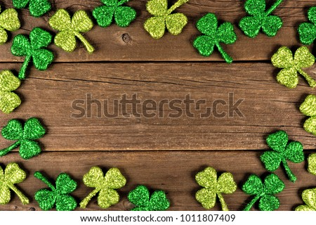 St Patricks Day frame of glittery shamrocks over an old rustic wood background